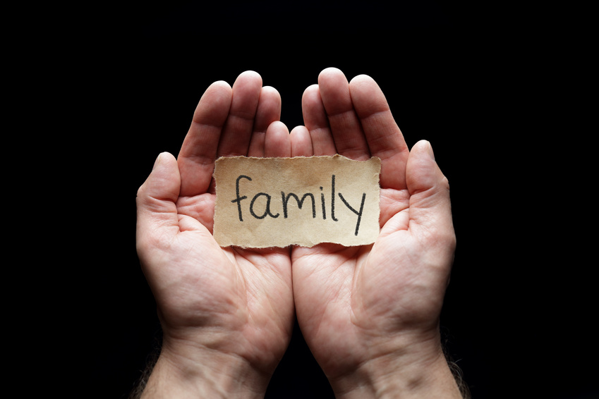 Family with the protection of cupped hands, concept for love, health, security and care